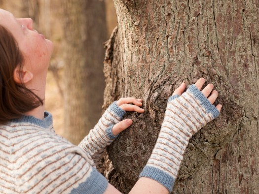 Josefin Waltin standing by a tree, wearing knitted gauntlets and a short sleeve sweater