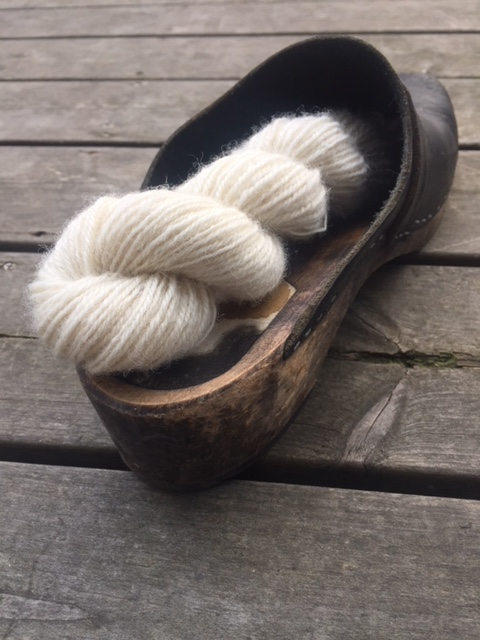 A skein of handspun white yarn in a clog