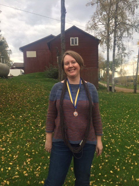 Josefin Waltin smiling with a bronze medal and a skein of yarn around her neck