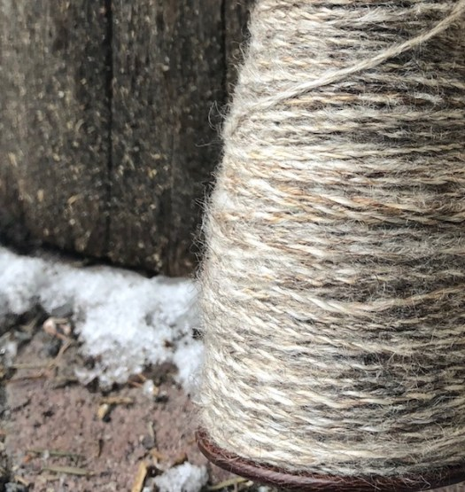 A spindle full of grey yarn
