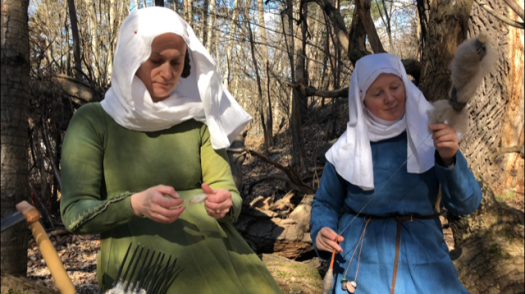 Two women dressed in medieval clothes, spinning and combing wool