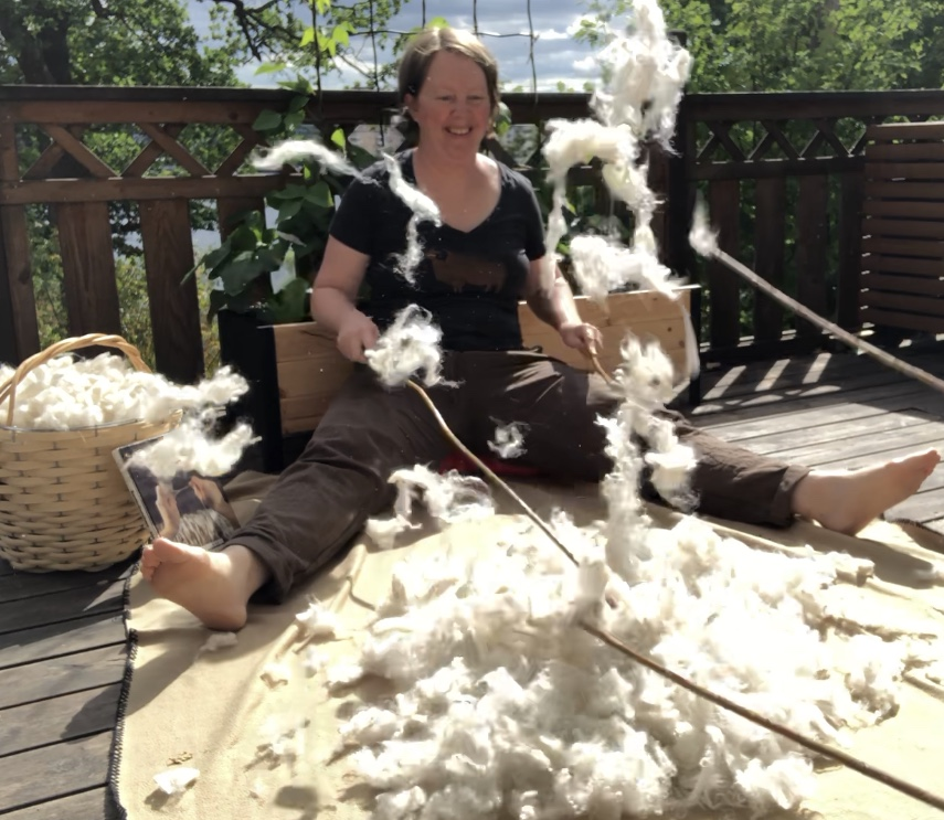 Josefin Waltin sitting with a pile of wool. Locks are flying in the air around her.