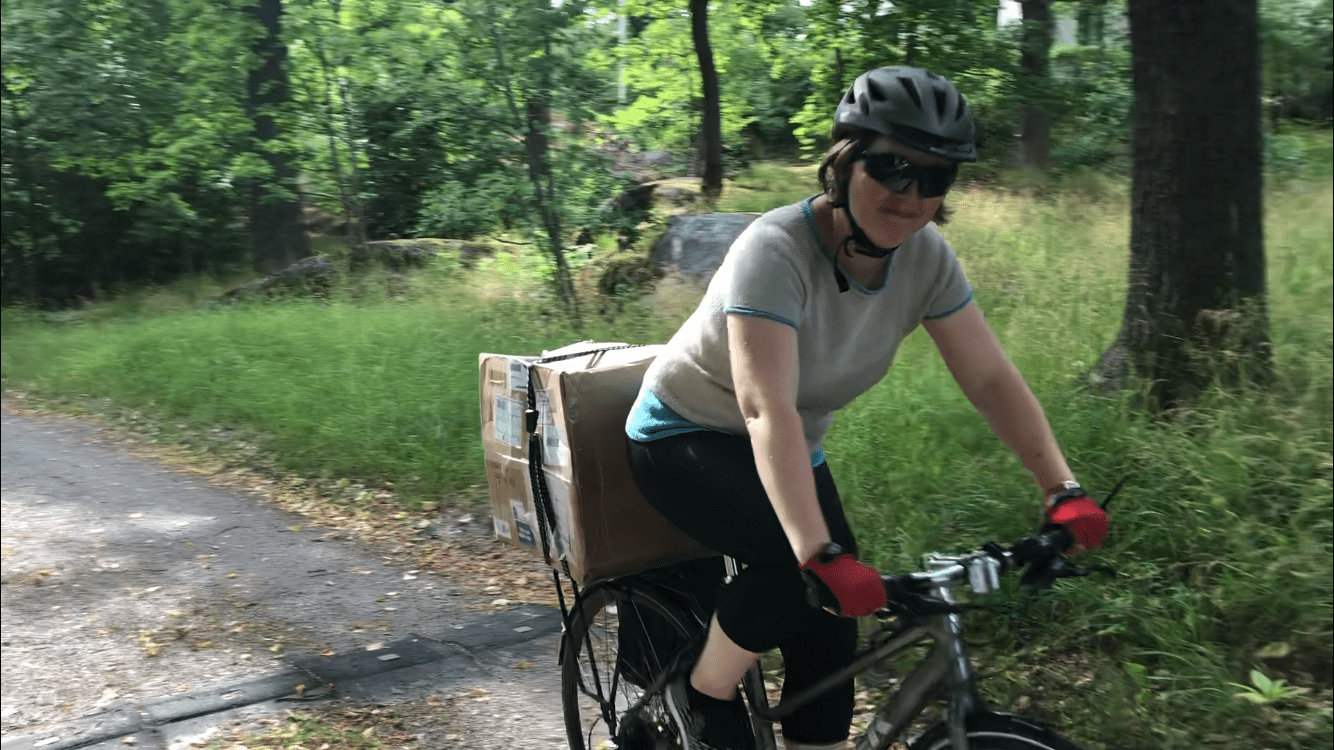 Josefin Waltin biking with a big box on the rack