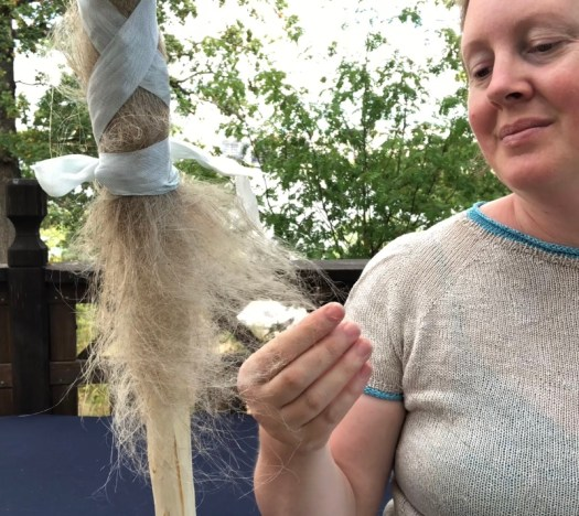 Josefin Waltin drafting flax fiber from a distaff.