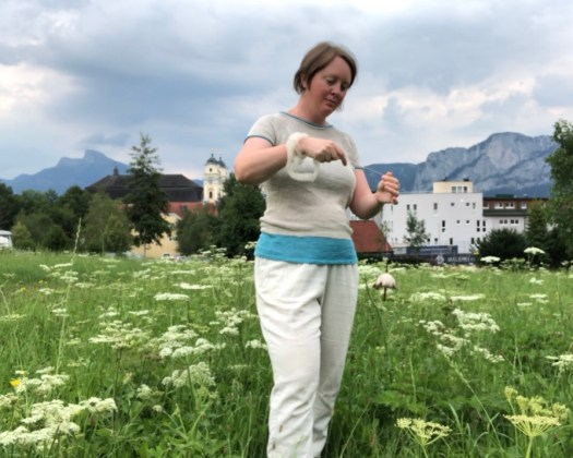 A person spinning on a spindle on a meadow. Mountains and a town in the background.