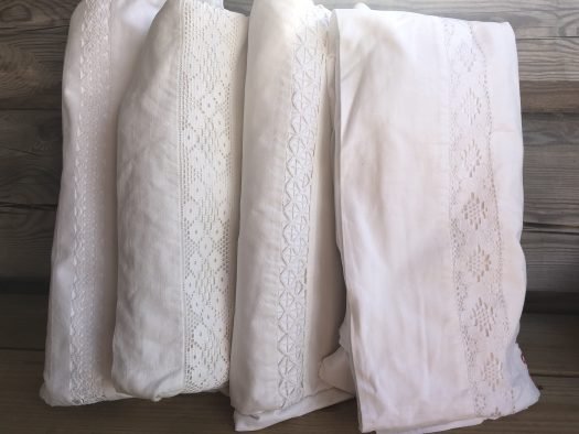 Four folded sheets with lace borders