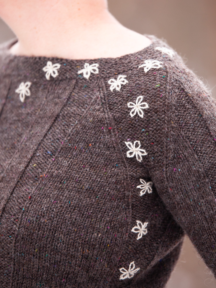Close-up of a grey sweater with white embroidered flowers