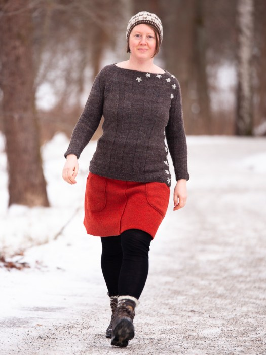 Josefin Waltin walking in the snow. She is wearing a dark grey knitted sweater with white flowers embroidered on the side.