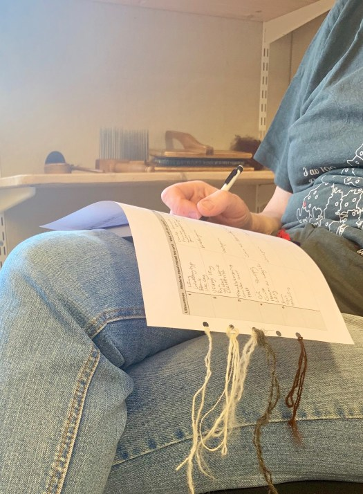 A person filling in a chart. Yarn samples are attached to the chart.