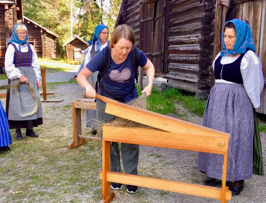 A woman breaking flax. Ladies in period costumes in the background.