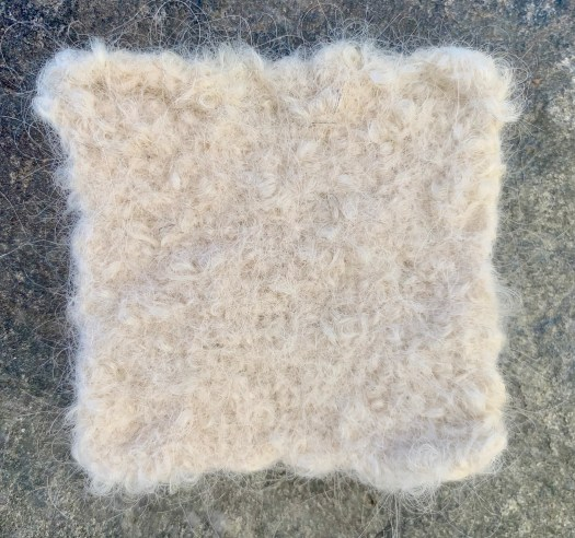 A white felted swatch. Little loops of scattered over the swatch.
