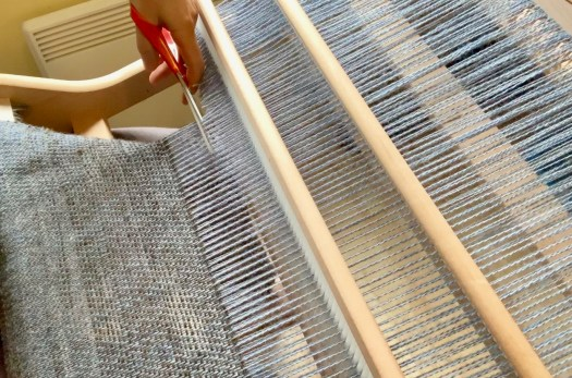 A hand cutting down a warp from a loom.