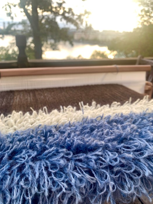 A table loom  with a rya weave on it. Sunrise over a lake in the background.