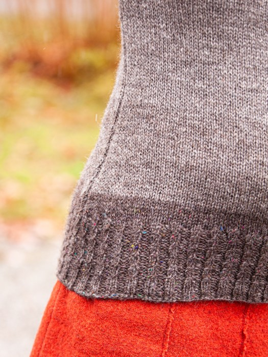 Close-up of the bottom hem of a knitted sweater. The hem has cabled ribbing.