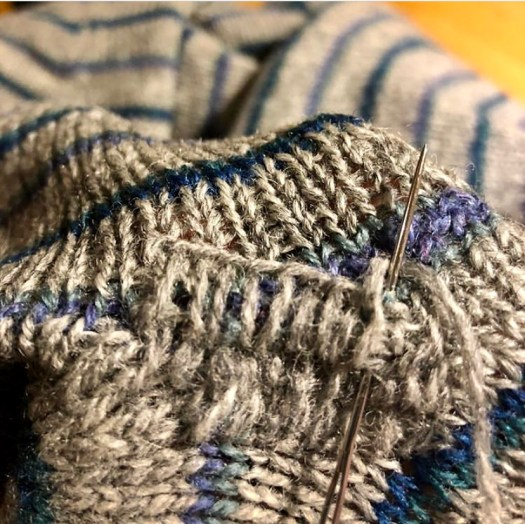 A darning needle mending a knitted sweater.