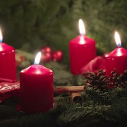 Advent candles are often used in preparation. The display is typically made up of four red candles arranged within a wreath.