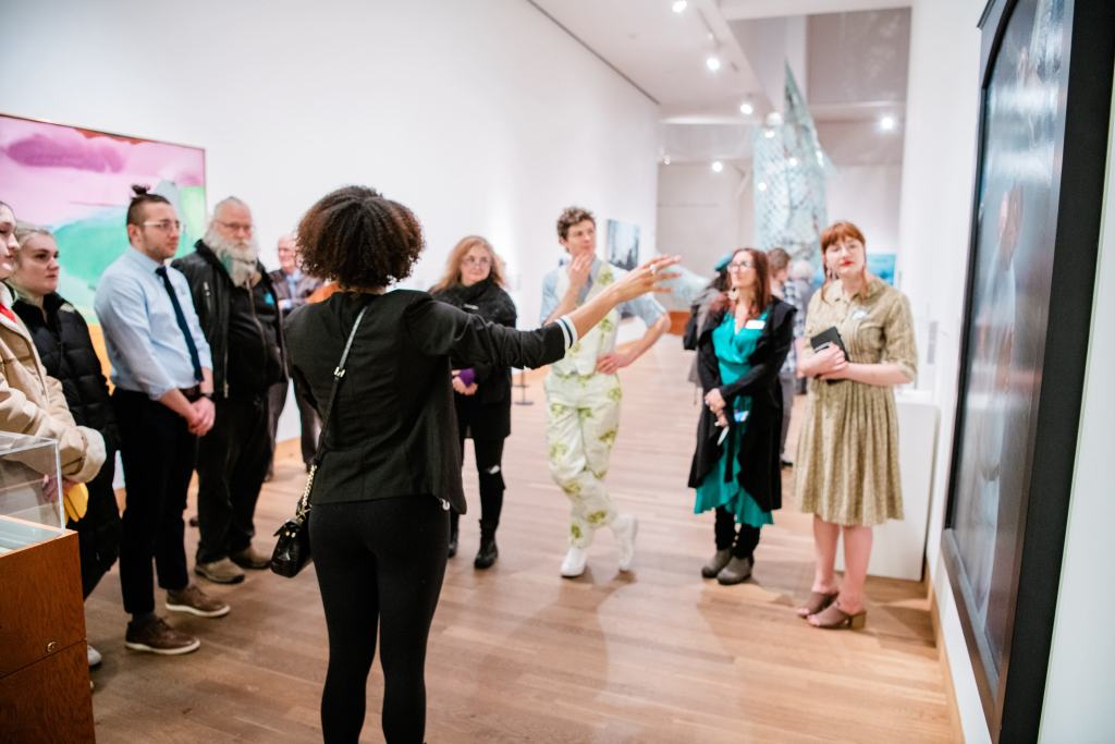 A student guide with her back turned to the camera exclaims about a painting on the wall; A group of 8 people form a semi-circle around her, listening intently