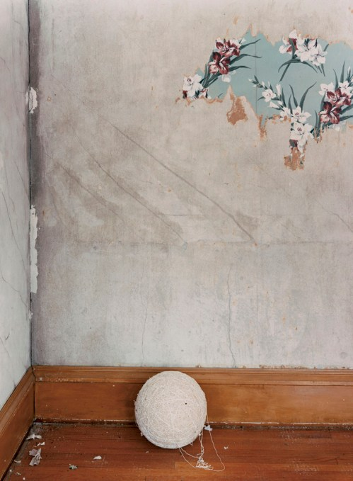 A photograph of a ball of string on a wooden floor in the corner of a room; a bit of floral wallpaper remains on an otherwise blank wall.