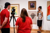 Artist Maya Beecham—a family member of Rose Smith— stands in front of Rose's paintings and provides an interview to two StoryMobile team members who record her using a camera on a tripod.
