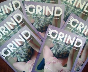 Copies of The Grind laid out in a pattern; The zine is purple and on the cover is an erotic dancer taking a selfie while mounted on a club patron.