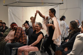 A dancer in a costume constrcuted of white medical gloves holds a seated audience member's hand above their head with during the Lifelong Choreographies performance.