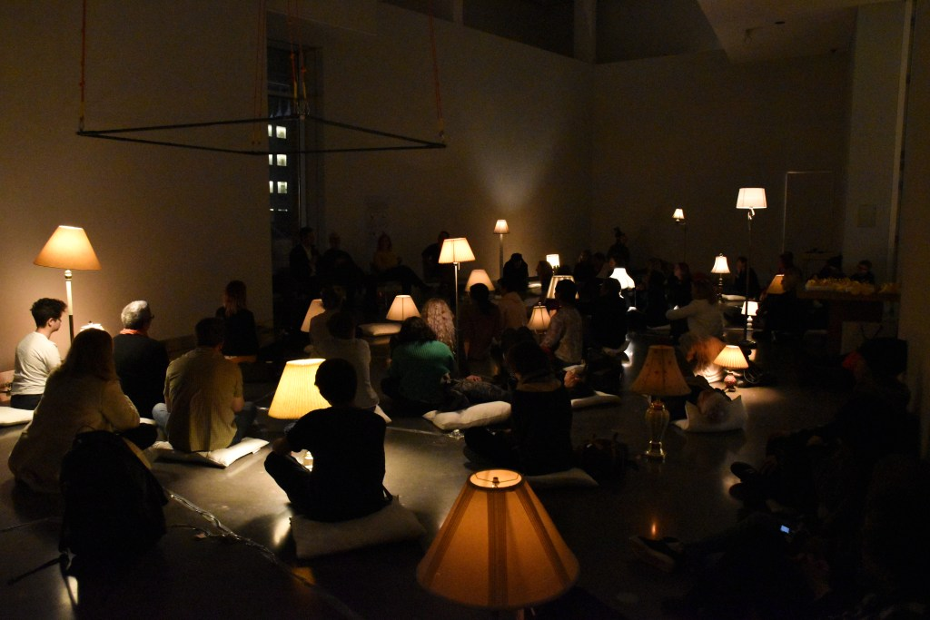 Audience members sit on pillows in a dark Target Studio Gallery lit only by lamp-light. Warm light emits from lamps installed all over the gallery. Peng Wu and Dr. Michael Howell discuss their research.