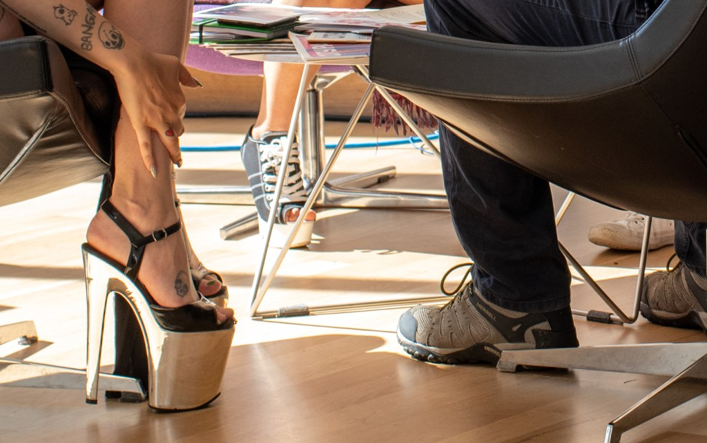 The photograph is of two individual's feet. The figure on the left is wearing metallic high heels and has a number of tattoos. The person at right is wearing athletic sneakers and jeans. They are in chairs next to each other and appear to be talking.