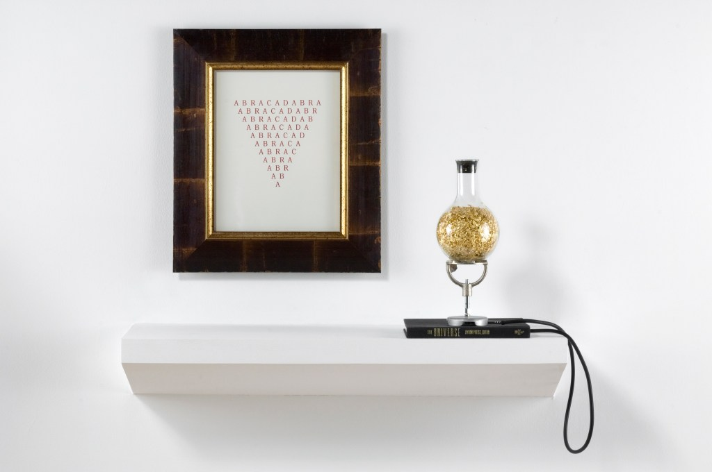 """A framed print of """"ABRACADABRA"""" in a downward-pointing traingle shape floats above a white shelf. To the right on the shelf are what looks like golden flakes in a scientific glass tube. It stands ontop of a book whose spine reads, """"The UNIVERSE"""""""