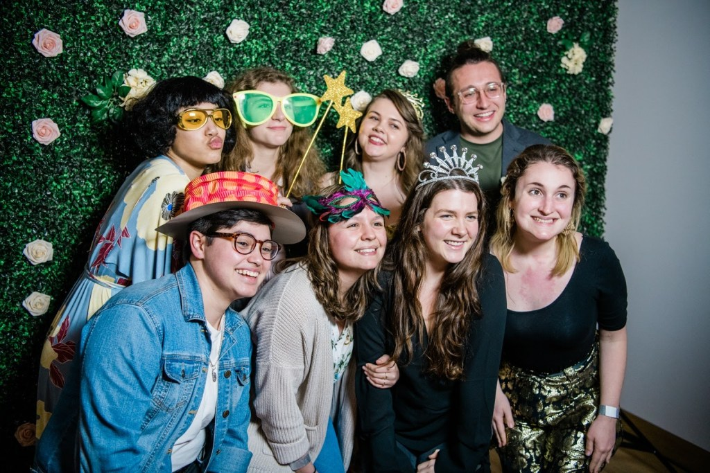 Eight students from the WAM Collective pose as a group smiling and wearing party hats and other props