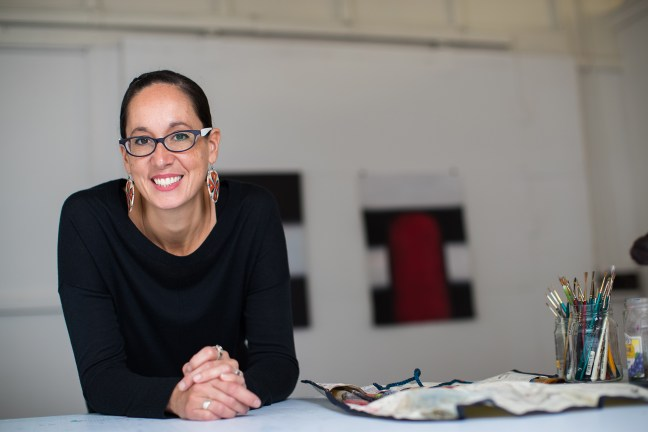 Artist Dyani White Hawk in her studio, leaning against at able and looking at the camera, smiling. She wears long colorful earrings, a black long-sleeve top, and medium black-framed glasses with her dark hair pulled back from her face
