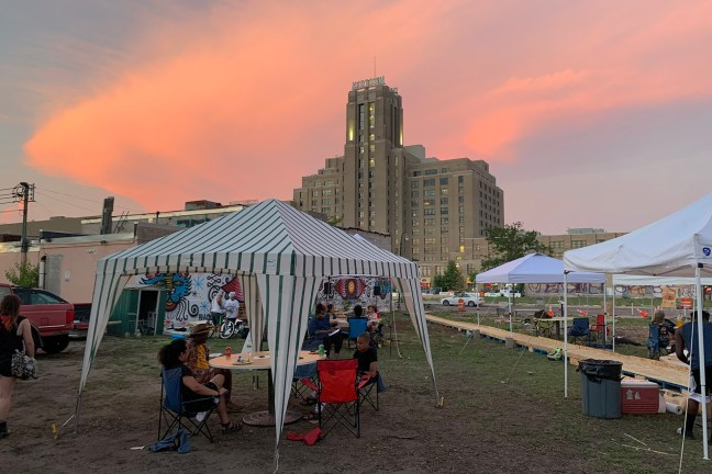 A tent on the Roberts Shoes Lot on Lake Street with the Midtown Exchange in the background and the setting sun.