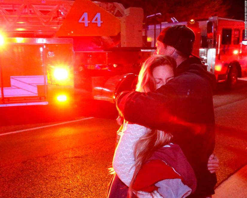 THOUSAND OAKS, CA - NOVEMBER 08: Molly Esterline is hugged by David Crawford on scene after a shooter wounded seven Wednesday night on November 8, 2018 in Thousand Oaks, California. The gunman burst into the bar around 11:20 p.m., cloaked in all black as he threw smoke bombs and began shooting at targets as young as 18 inside the Borderline Bar