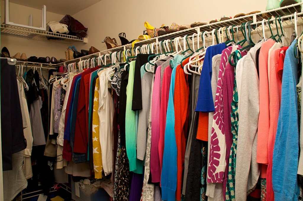 Looking into a full walk in closet belonging to a woman. Full of clothing, hangers, shelves and shoes.