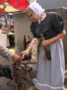 Vrouw in oude Scheveningse klederdracht bij een spinnewiel