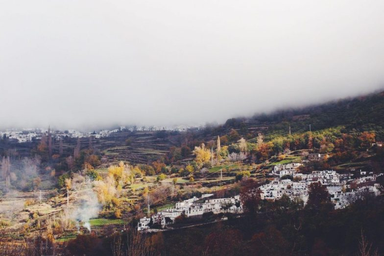 A village of white buildings on a mountainside in Spain, with thick fog overhead.