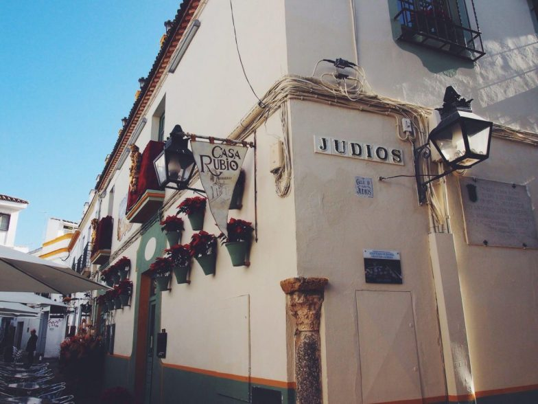 A pretty street corner with the name 'Judios' on one of the buildings.