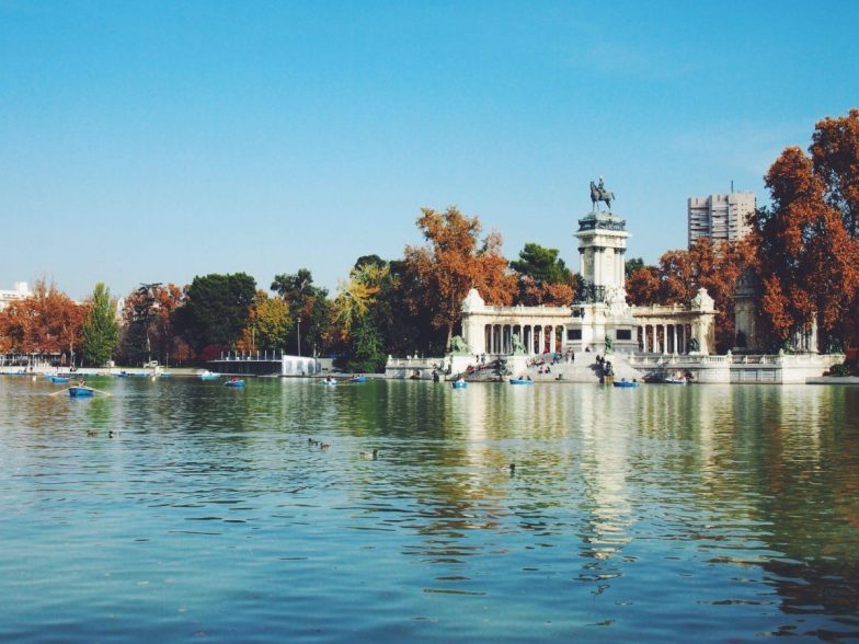 A vast blue lake surrounded by historic buildings and fall foliage.