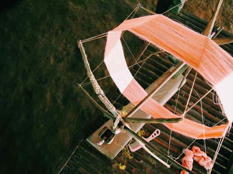 Pink threads on a wooden spinning wheel.
