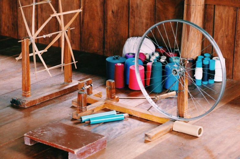 A spinning wheel and spools of colourful thread strewn across a wooden floor.