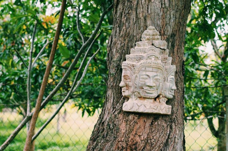 A Khmer Buddhist icon mounted to the trunk of a tree.