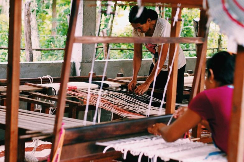 Two women working together on looms at Cambodian Weaving Village.