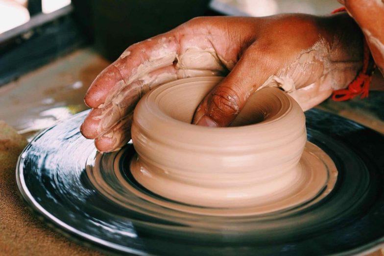 Close up of a hand on a clay pot that's on the spinning wheel.