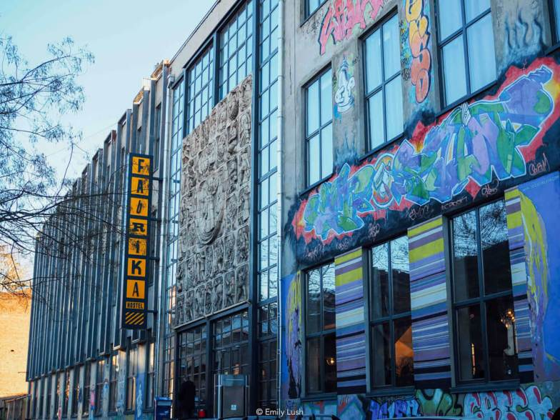 A huge industrial building covered with graffiti and marked with a yellow sign that says 'Fabrika Hostel'.