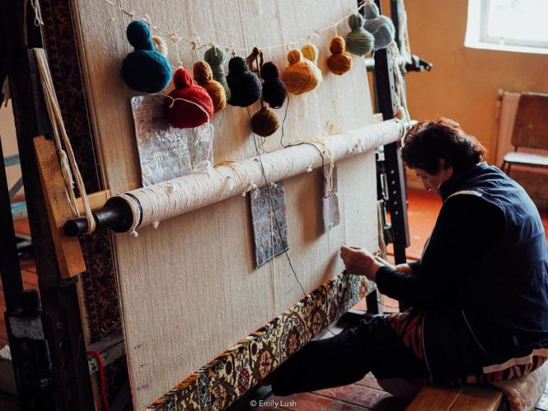 A woman works at a carpet loom with colourful balls of wool.