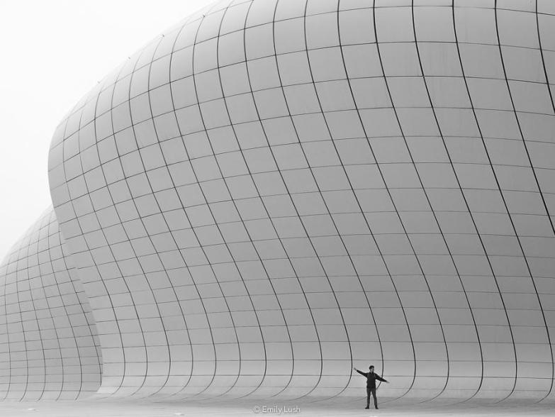 A man stands against a white curved wall with his arms outstretched.