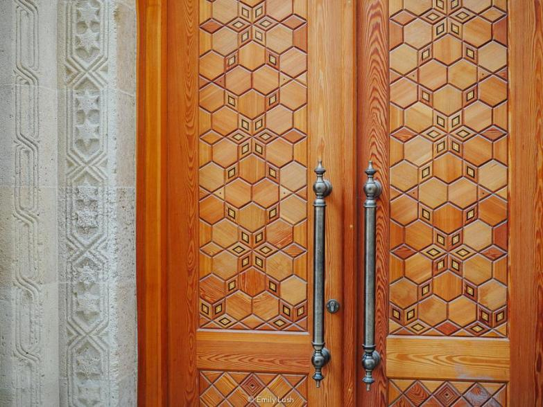 A heavy wooden door with a beautiful Islamic pattern.