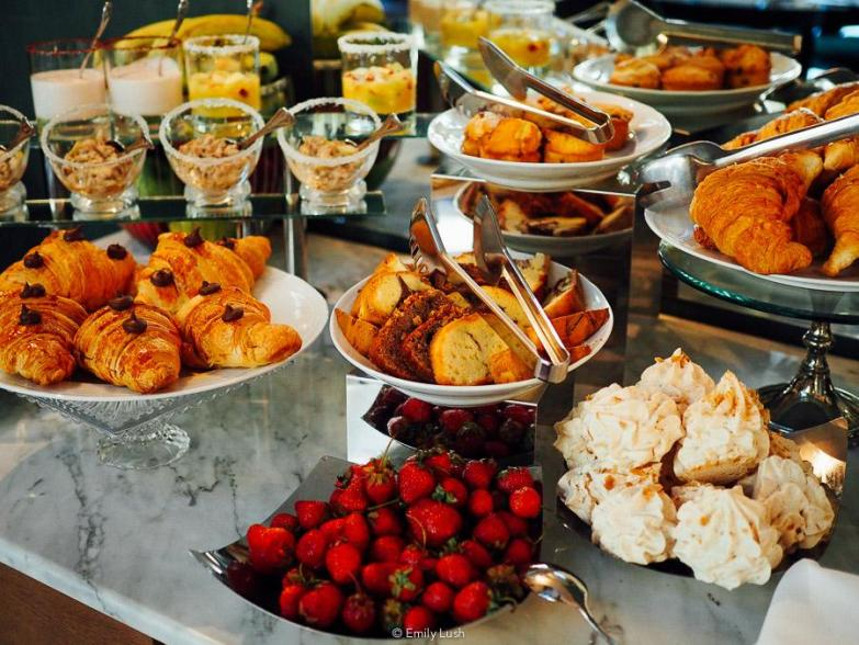 A hotel breakfast buffet spread including strawberries and croissants.