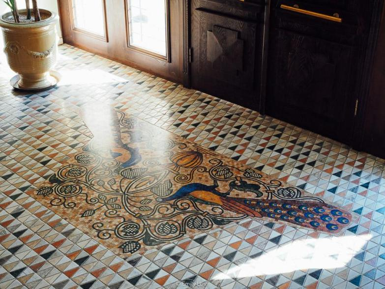 An ornate floor mosaic featuring a pair of blue peacocks.