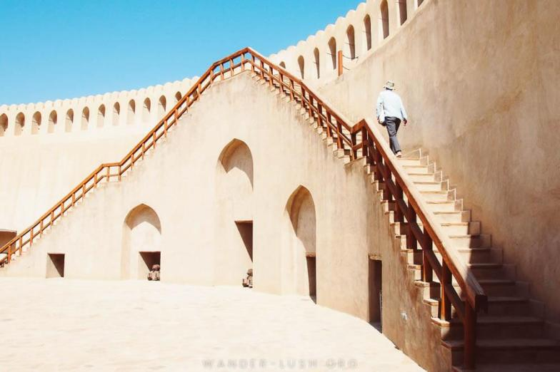 A man walks up a staircase along the side of Nizwa Fort.