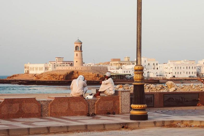 Two men chatting in front of the ocean in Sur, Oman. Photo credit: Copyright Emily Lush | Oman road trip